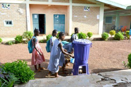 Deklice v Gvineji si umivajo roke v vodnjaku.