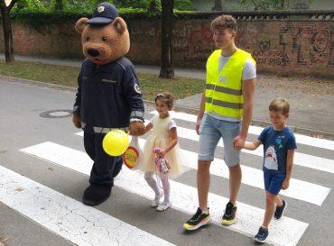 Policist Leon in dijaki dveh ljubljanskih srednjih šol ves teden prvošolcem pomagajo čez cesto. Vir: Policija