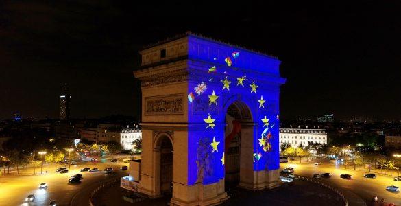 Tako je v barvh evropske zastave žarel Slavolok zmage v Parizu leta 2018, tedaj tudi še z britansko zastavo. Na fotografiji se vidi tudi slovenska. Vir: EC - Audiovisual Service