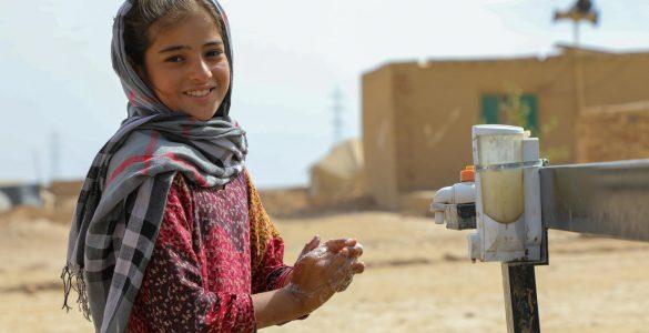 Devetletna Afganistanka Marjam si pere roke z vodo in milom, ki ju je za begunsko taborišče Ferdusi priskrbel Unicef. Foto Omid Fazel/Unicef