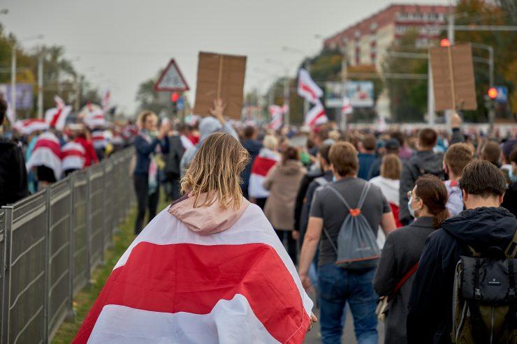 Protestnica, ovita v zastavo, ki je simbol protestnikov, na protivladnih demonstracijah oktobra 2020. Vir: Adobe Stock